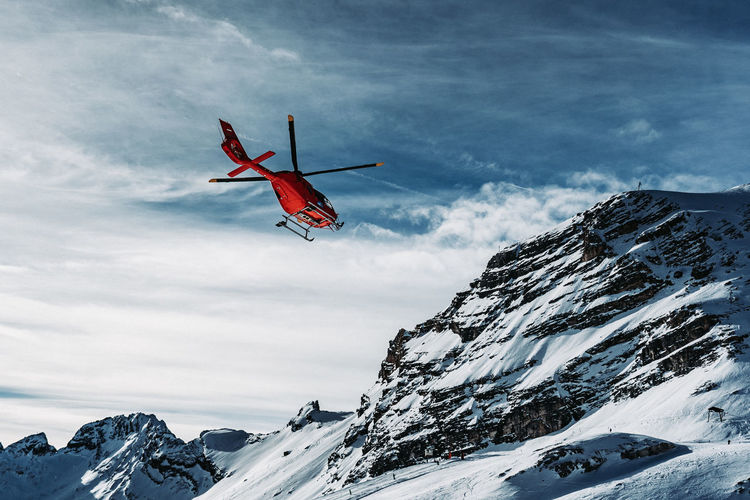 Helicopter flying over snowcapped mountains against sky