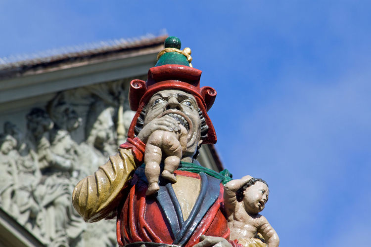 Low angle view of child-eating statue against blue sky