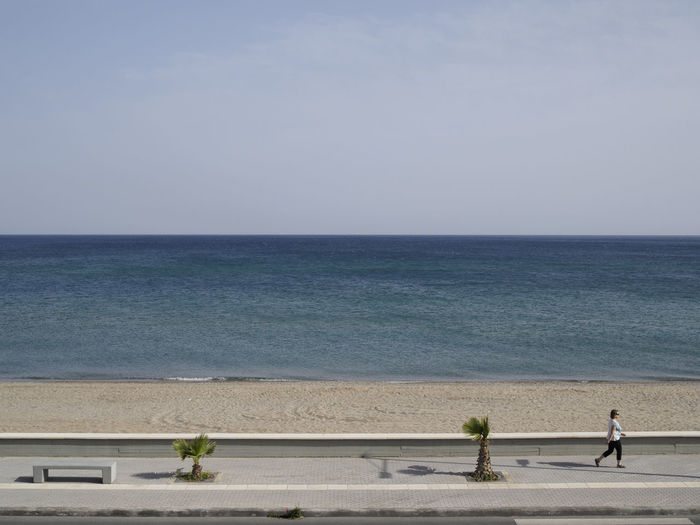 person walking on the pavement in front of the beach at Rethymno Crete in the morning Beach Clear Sky Day Horizon Over Water Outdoors Pavement Sea Shadow Streetphotography Tranquility Vacations Water Women