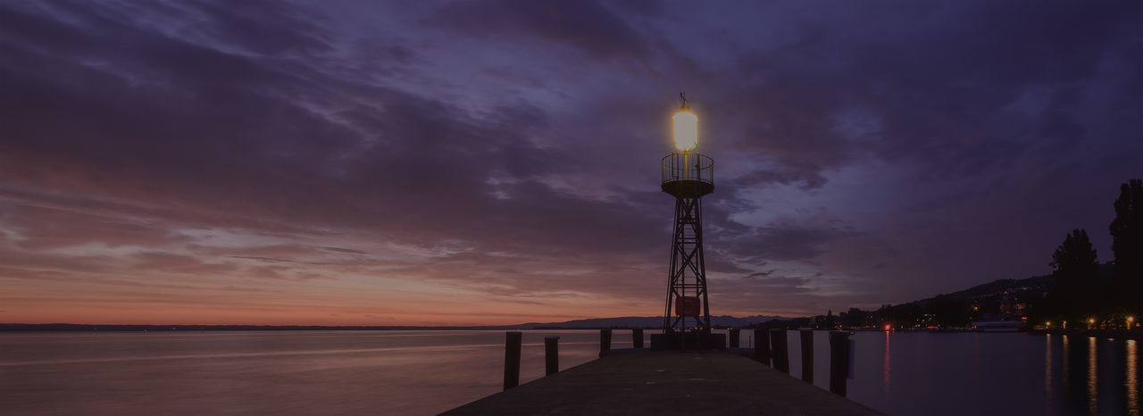 Illuminated tower by sea against sky at sunset
