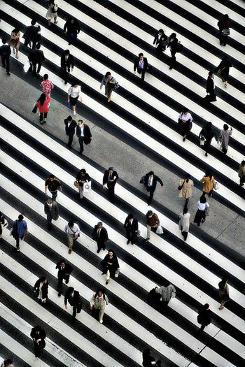 High angle view of people crossing road in city
