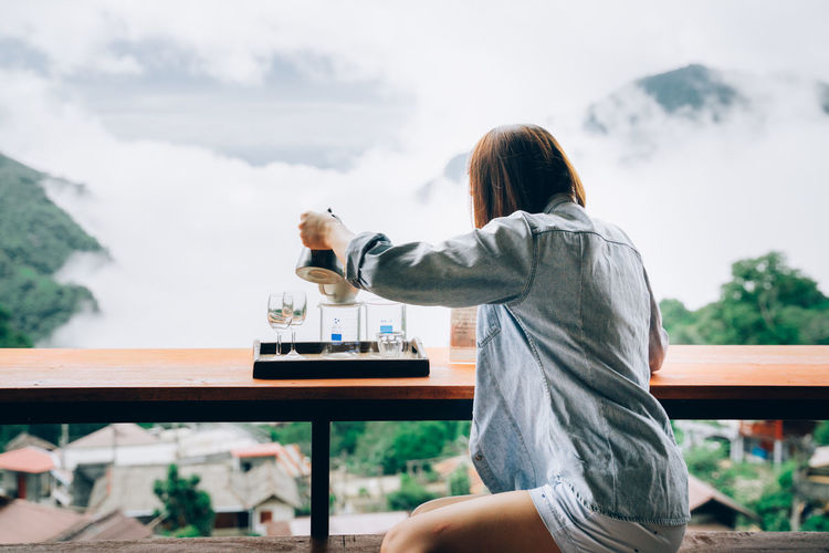 Rear view of woman sitting at table against sky