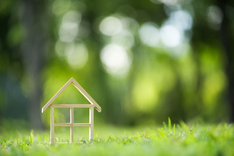 Close-Up Of Wooden Model Home On Grassy Field