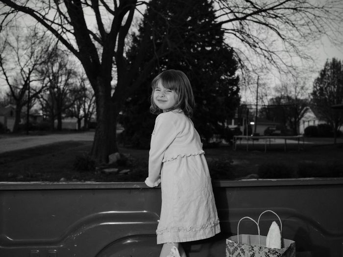 Portrait Of Girl Standing In Pick-Up Truck At Park