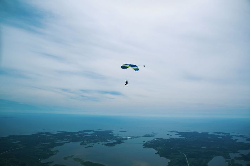 Person paragliding over sea against cloudy sky