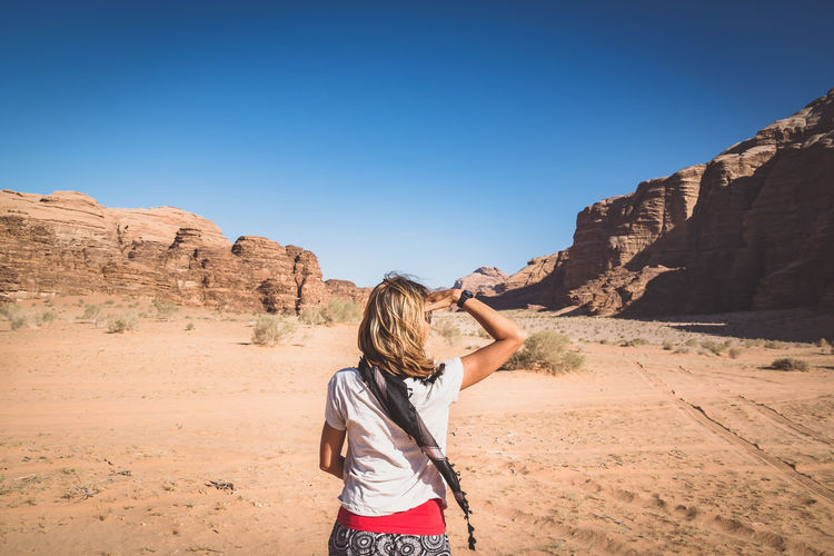 Rear View Of Woman With Head In Hand Standing At Desert