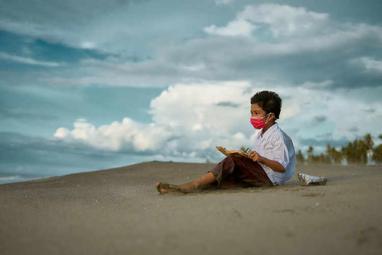 Boy sitting on beach by sea against sky