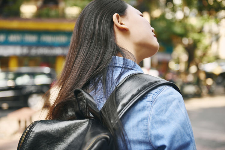 Woman with long hair carrying backpack in city