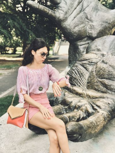 Woman sitting on hand of statue while looking at wristwatch