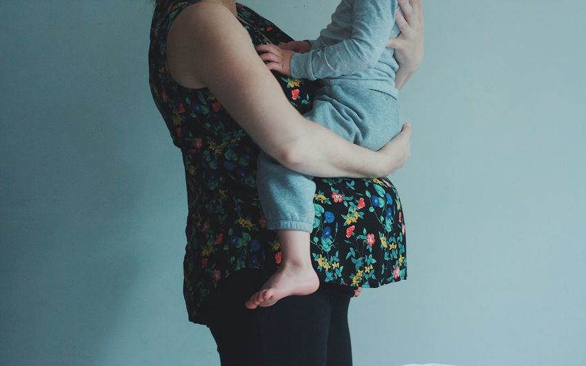Cropped Image Of Pregnant Woman Carrying Son While Standing Against Wall