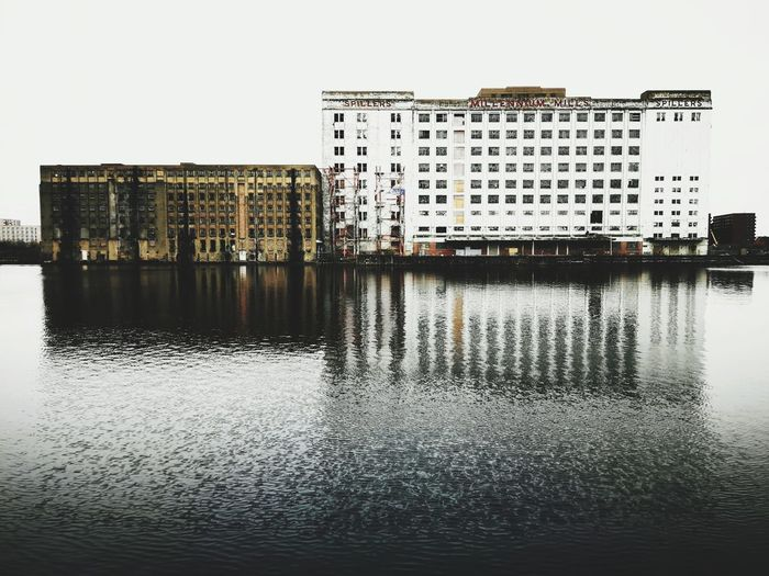Reflection of buildings in river against clear sky