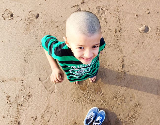 High angle portrait of cute boy standing on sand at beach