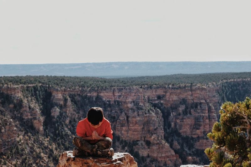 Boy mediating while sitting on rock formation against clear sky