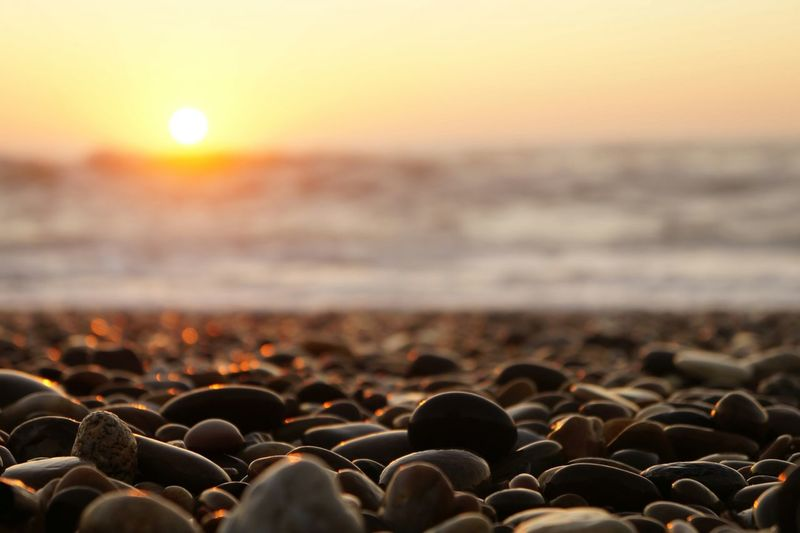 Stones At Beach Against Sky During Sunset