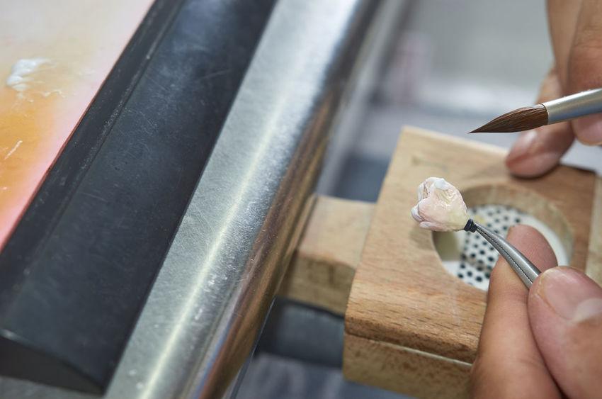 Closeup of dental technician putting ceramic to dental implants in his laboratory. Dental Dentist Dentistry Doctor  Man Prosthodontics Restoration Working Articulador Brush Careful Cavity Ceramic Close-up Denture Implant Inlay Laboratory Metal Professional Prothesis Technician Technologist Teeth