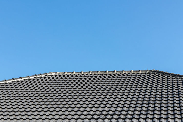 Low angle view of building roof against clear sky