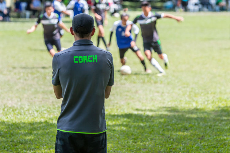 Male soccer or football coach watching his team competing Football Athlete Coach Competition Competition Sportsman Game Grass Men People Playing Field Rear View School Soccer Sport Sunny Day Uniform
