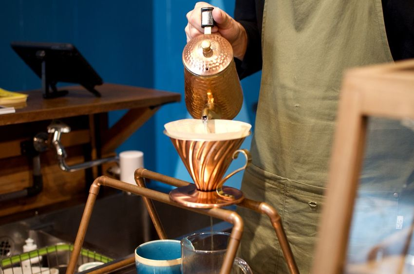 A barista in Osaka pours hot water over freshly ground coffee using handmade copper items. Food And Drink Focus On Foreground Coffee Handmade Handcrafted Pouring Coffee Pour Over Coffee Copper Details Commerce Small Business Morning Routine Thoughtful Japan Travel