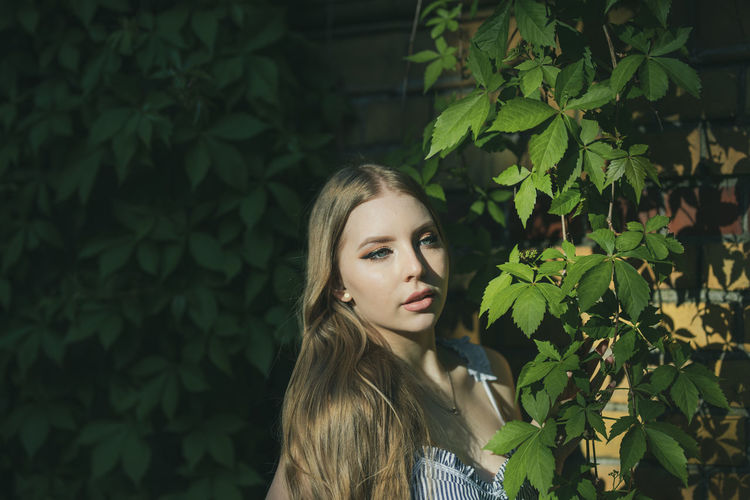 Thoughtful beautiful young woman standing by plants in park