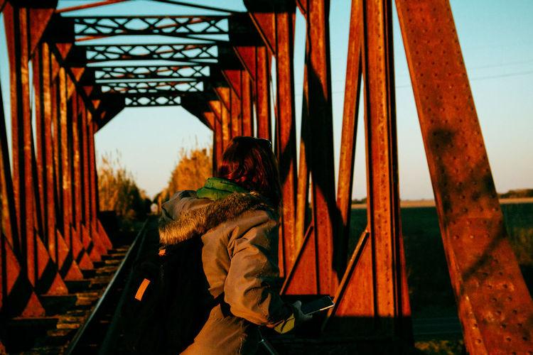 Rear view of people standing on bridge