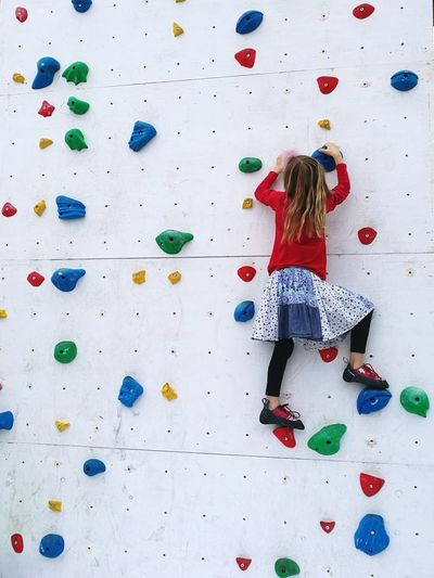 Rear View Of Girl On Climbing Wall