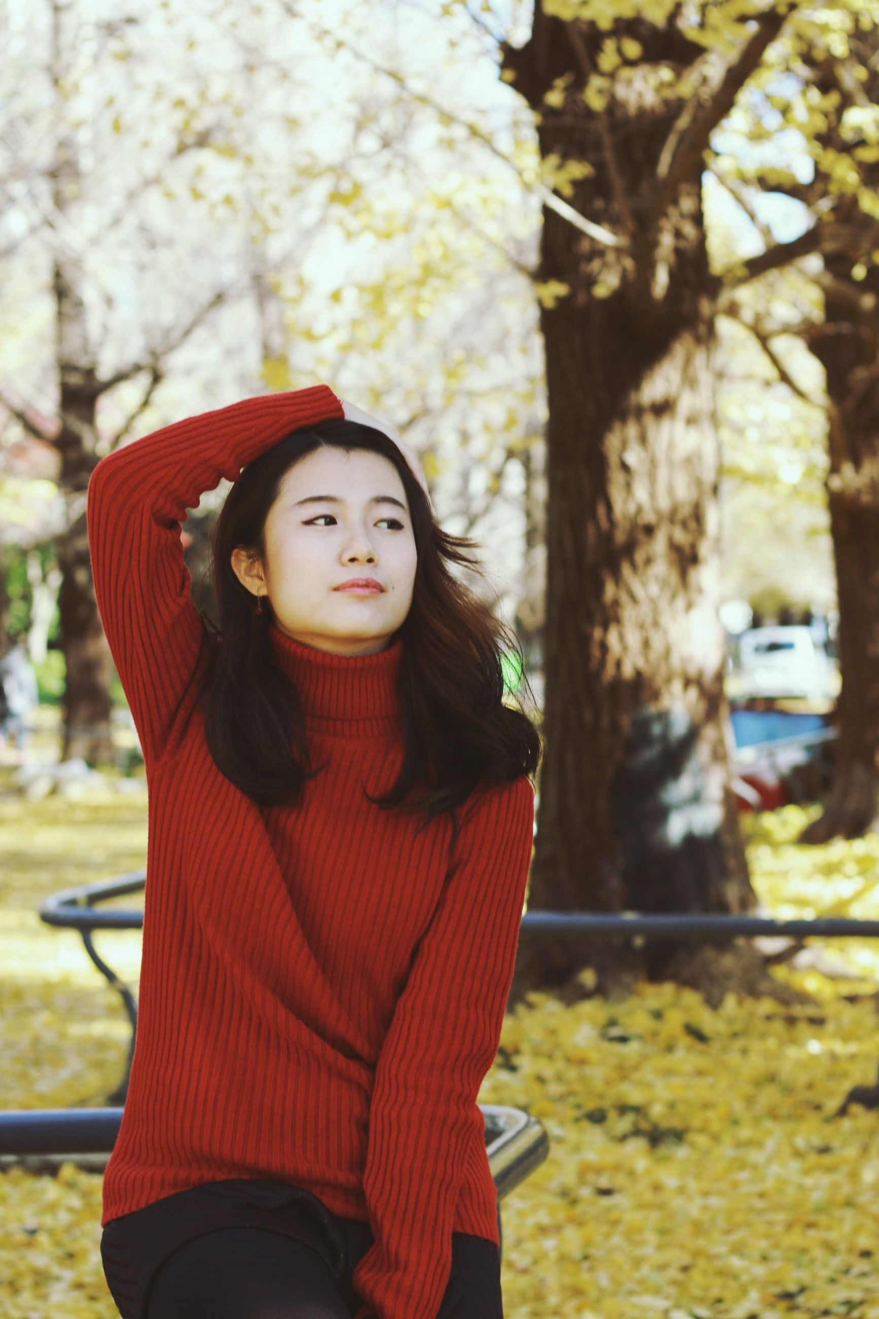young adult, looking at camera, lifestyles, portrait, person, casual clothing, focus on foreground, young women, standing, front view, leisure activity, smiling, three quarter length, tree, waist up, red, long hair