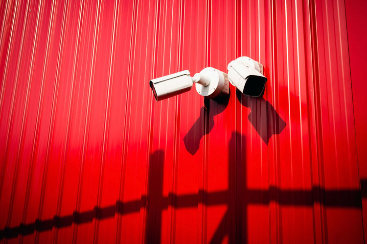 A low angle view of a cctv camera against a red wall