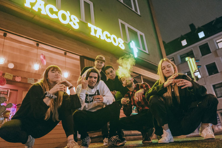 Group of people sitting outside building at night