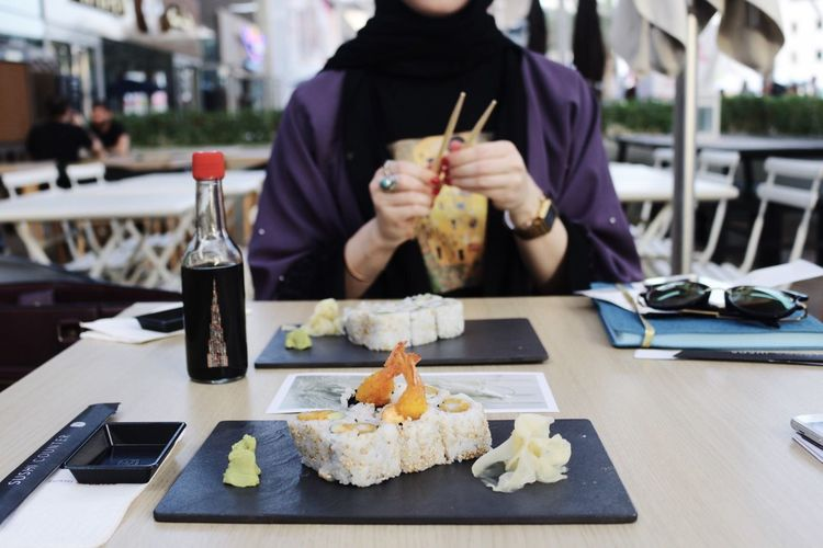 Midsection Of Woman Having Sushi At Restaurant
