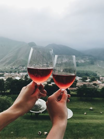 Two glasses of rose wine in two hands in fronf of mountains
