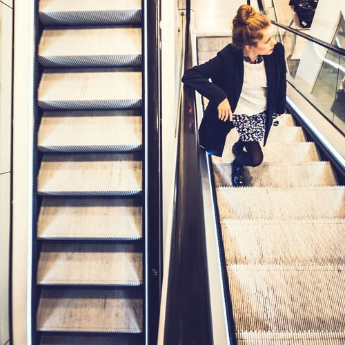 High Angle View Of Woman Standing On Escalator At Shopping Mall