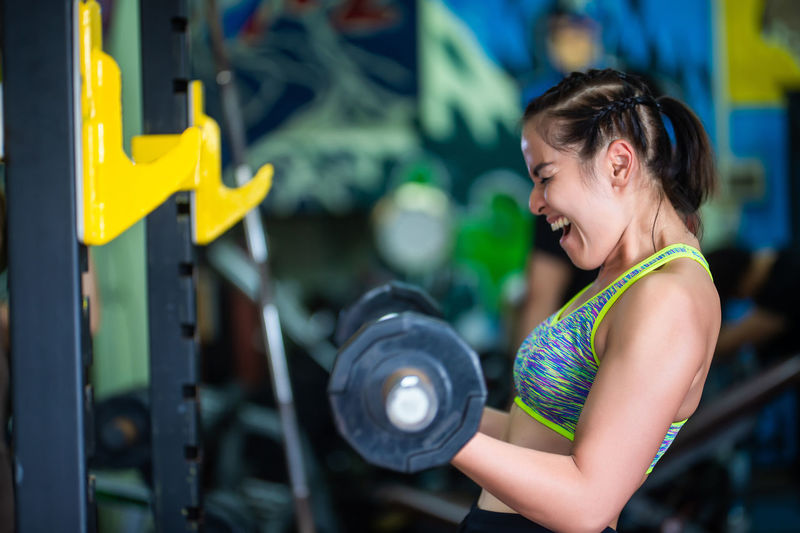 woman work out in gym Adult Brown Hair Clothing Exercising Females Focus On Foreground Hairstyle Happiness Healthy Lifestyle Indoors  Lifestyles One Person Real People Side View Smiling Waist Up Weight Training  Women Young Adult
