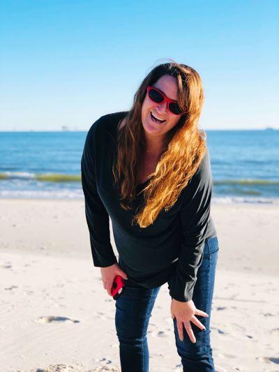 Portrait of happy mature woman wearing sunglasses at beach