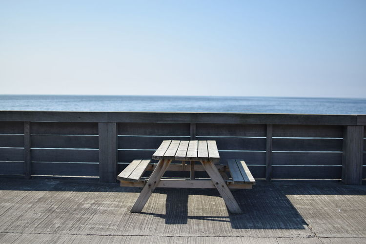 Picnic table at promenade on sunny day