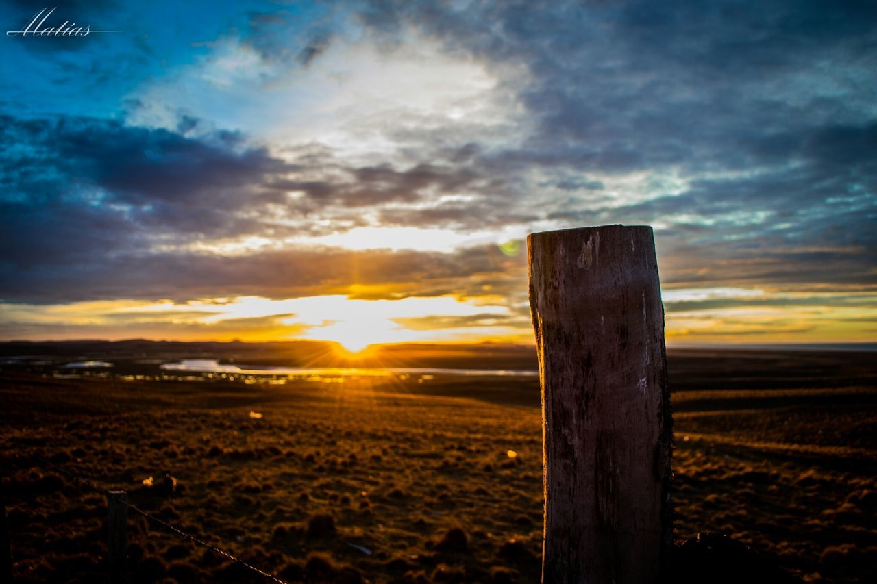 sunset, cloud - sky, sky, nature, scenics, field, beauty in nature, dramatic sky, tranquility, no people, landscape, tranquil scene, outdoors, wooden post, close-up, day