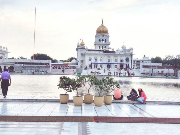 People at gurudwara bangla sahib against sky