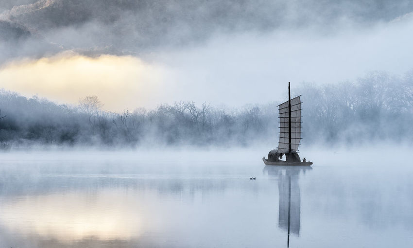 Water Fog Waterfront Lake Tranquil Scene Beauty In Nature Tranquility Reflection Scenics - Nature Sky Nature No People Cloud - Sky Non-urban Scene Day Outdoors Idyllic Cold Temperature Sailboat