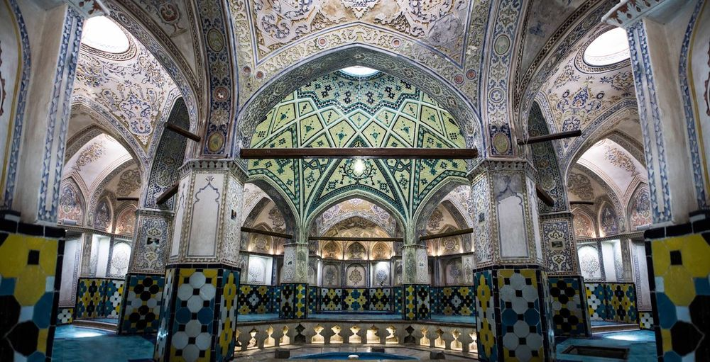 Sultan Amir Ahmad Bathhouse, with an area of around 1000 square meters, consists of two main parts: the sarbineh (dressing hall) and garmkhaneh (hot bathing hall). The sarbineh is a large octagonal hall and has an octagonal pool in the middle, separated by 8 pillars from the outer section. There are four pillars in the garmkhaneh, which make smaller bathing rooms all around as well as the entrance section to the khazineh (final bathing room) in the middle. The interior of the bathhouse is decorated with turquoise and gold tilework, plasterwork, brickwork, as well as artistic paintings. The roof of the bathhouse is made of multiple domes that contain convex glasses to provide sufficient lighting to the bathhouse while concealing it from the outside. Historical Place Historical Building History Iranian Architecture Iranian Art Iran Architecture Bathhouse Iran Kashan Arch Architecture Ceiling Religion History Place Of Worship Indoors  No People Day Colour Your Horizn EyeEmNewHere Stories From The City The Architect - 2018 EyeEm Awards