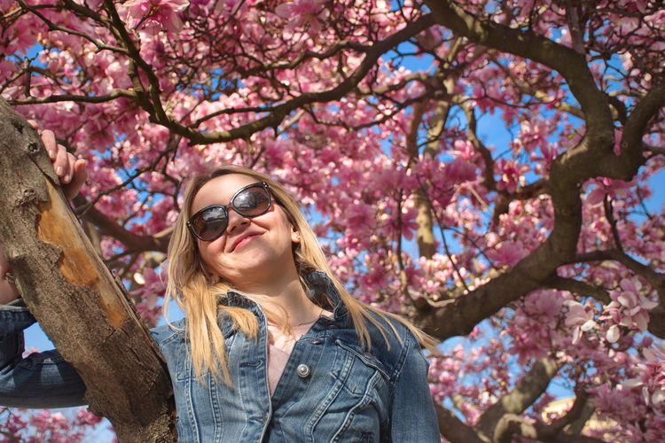 Tree Plant Young Adult One Person Sunglasses Young Women Leisure Activity Casual Clothing Glasses Hair Hairstyle Portrait Flower Long Hair Headshot Flowering Plant Nature Lifestyles Springtime Fashion Outdoors Beautiful Woman Magnolia Blooming Jeans Blond Hair Pink Color