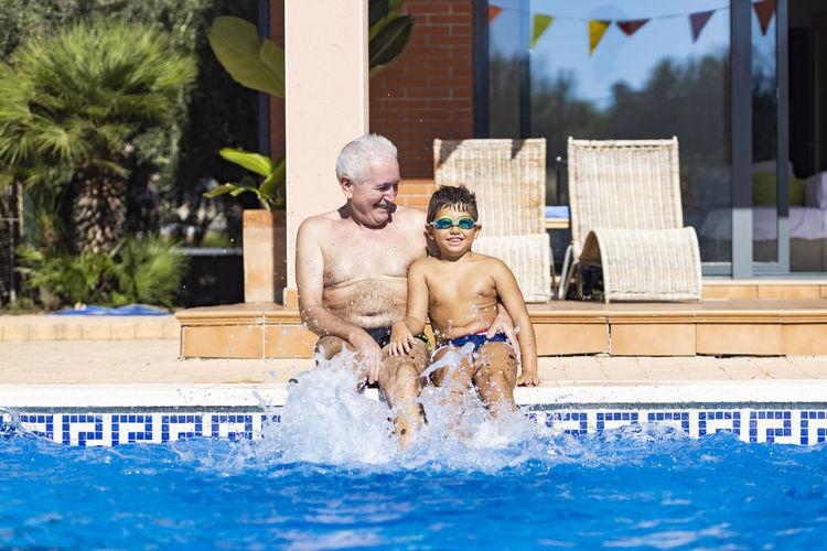 Full length of shirtless man swimming in pool