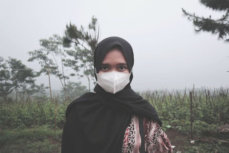 Portrait of young woman make a mask standing on field against sky