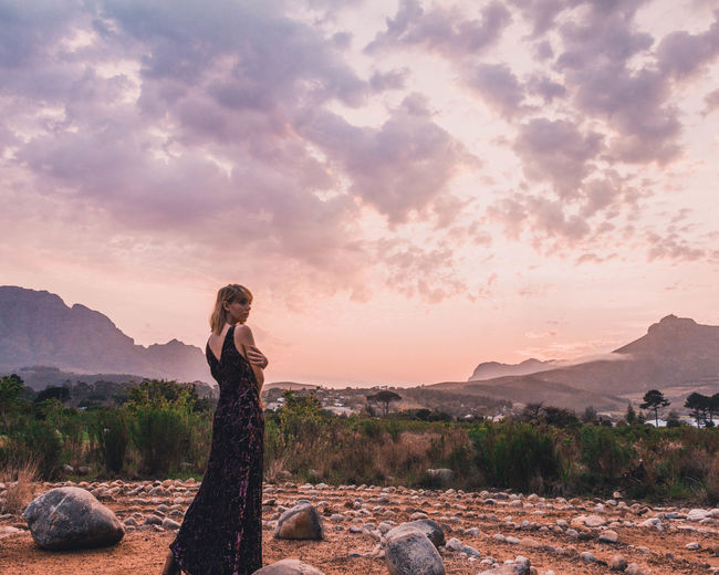 Woman standing on rock against sky during sunset