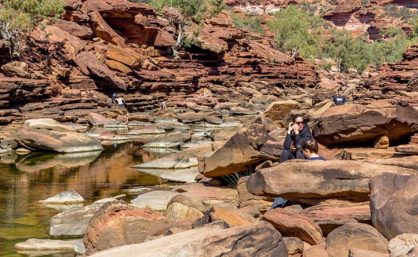 Man sitting on rock at shore