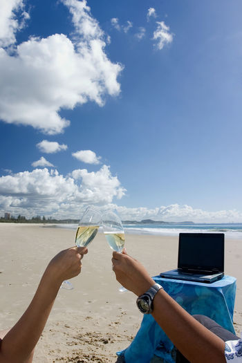 Cropped Hands On People Toasting Champagne Flutes At Beach