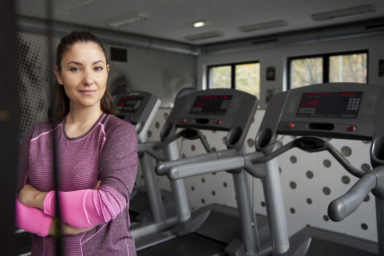 Portrait of woman with arms crossed standing in gym