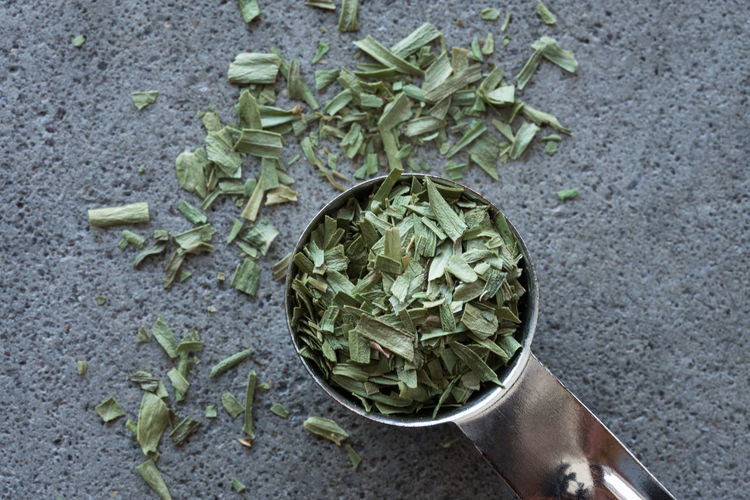 High Angle View Of Dried Herbs In Teaspoon