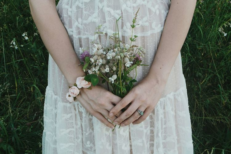 Midsection Of Woman Holding Flower Standing Against Plants