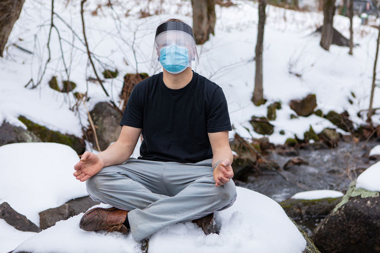 Man sitting on snow covered land