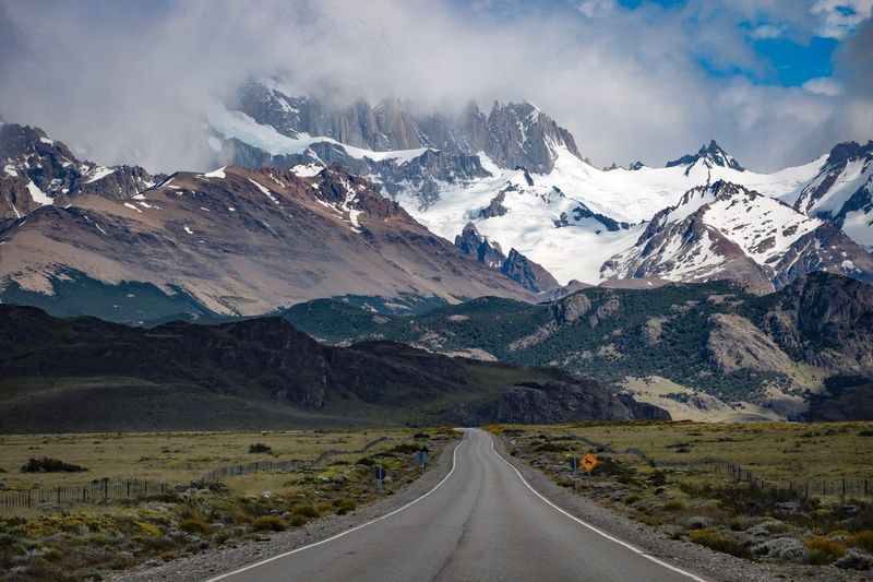 Empty road amidst snowcapped mountains against cloudy sky