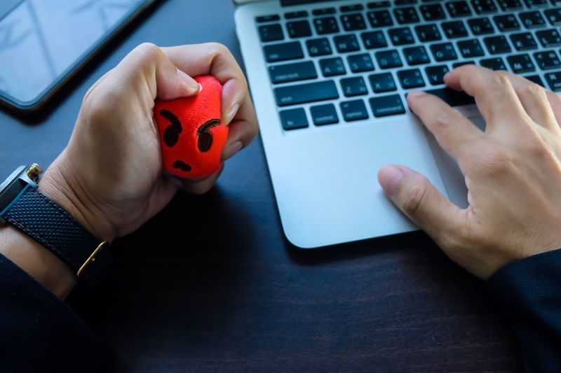Cropped hand of businessman pressing stress ball while using laptop on table